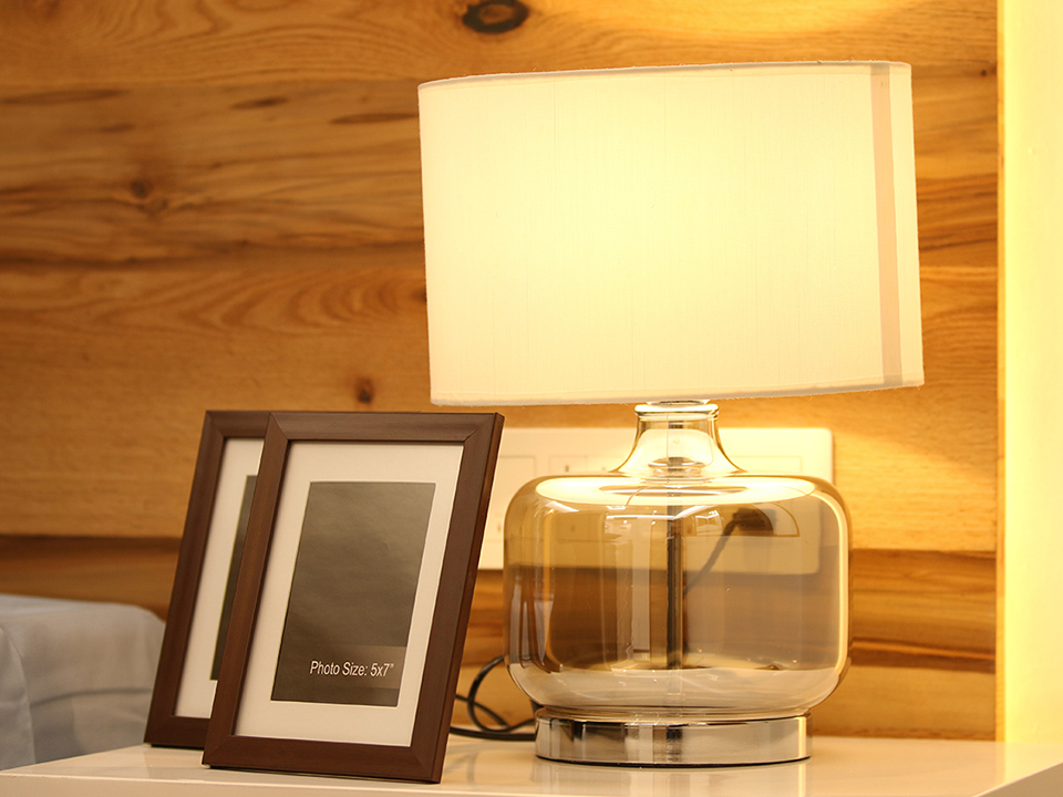 A simple arrangement on a bedside table, decorated with photo frames and a warm yellow lamp.