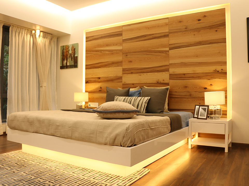 A bright bedroom whose interior has been styled with wooden furnishings and neutral tones of beige and white.