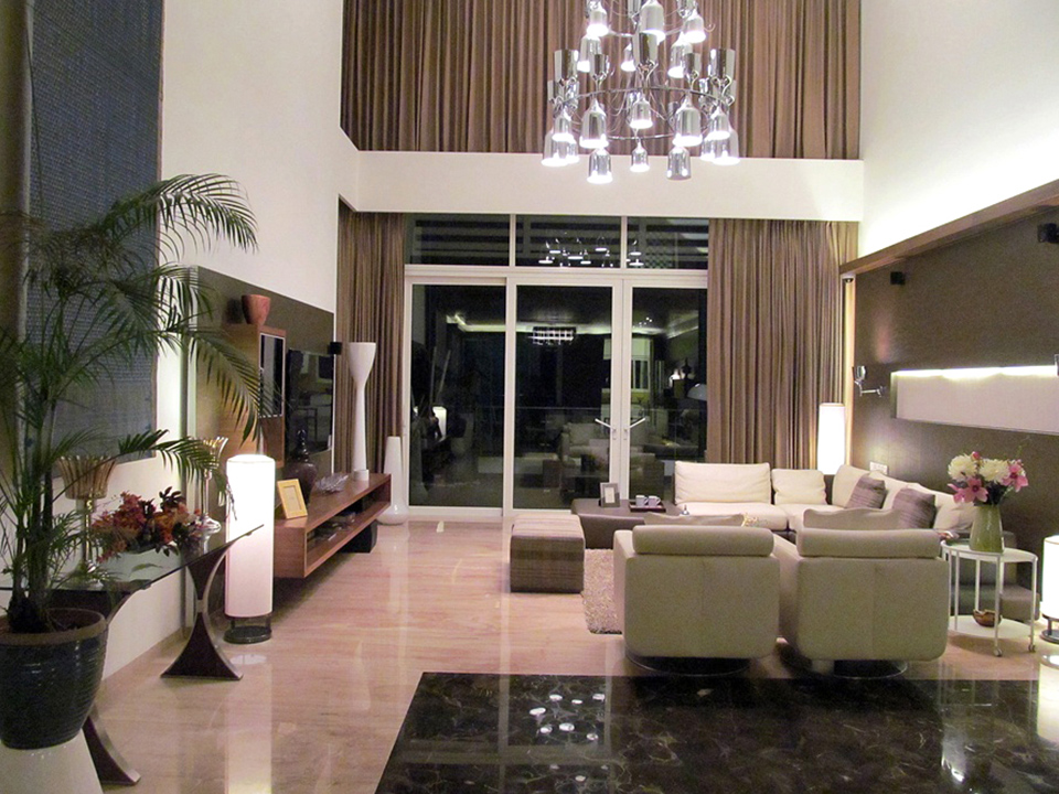A contemporary living room, decorated in glass furnishings and warm neutral tones.