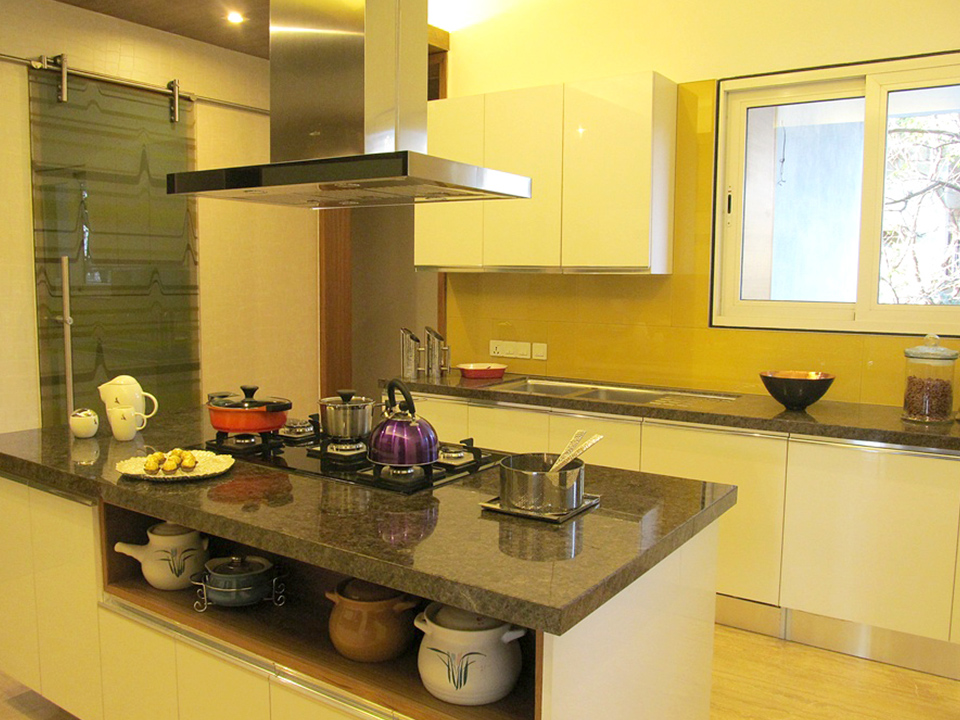 A bespoke kitchen whose interior has been styled and fitted with marble countertops and colorful furnishings.