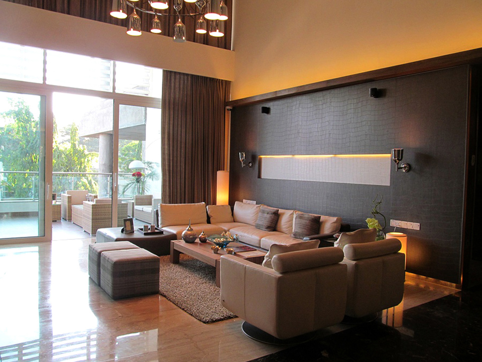 A plush living room, styled with darker toned furnishings and warm yellow lighting.