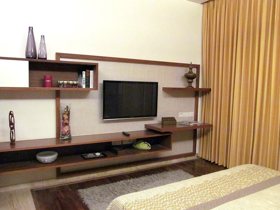 A bedroom furnished with wooden furniture with a television and colourful artifacts.