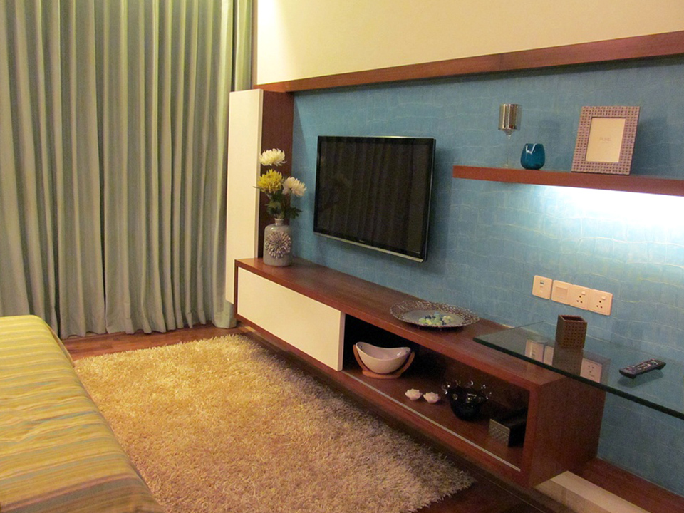 A blue bedroom wall furnished with wooden furniture with a television and colourful artifacts.