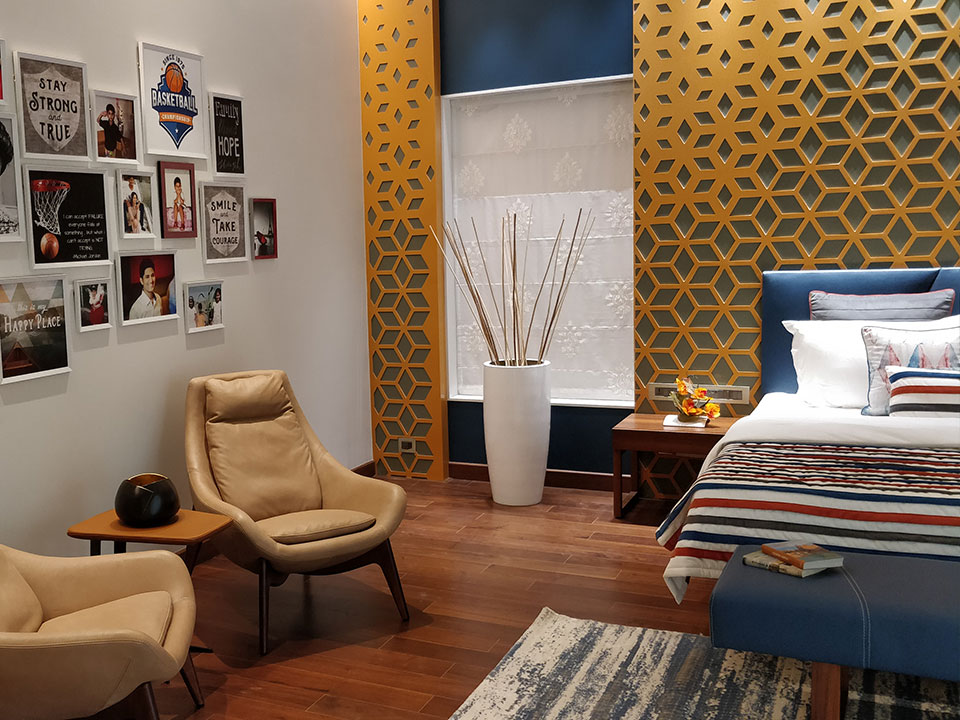 A bedroom with a small sitting area in neutral tones, wooden flooring, and a unique geometric pattern on the walls.