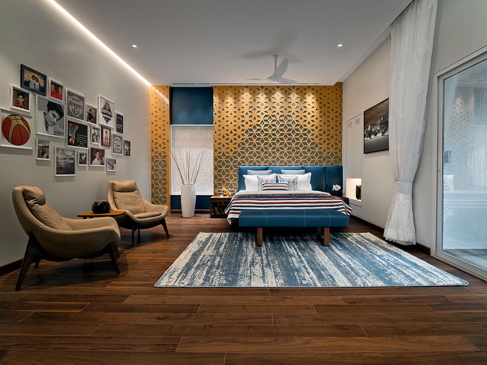 A bespoke bedroom with a geometric pattern on the walls, blue bedding and a sitting area accompanied by personal photo frames.