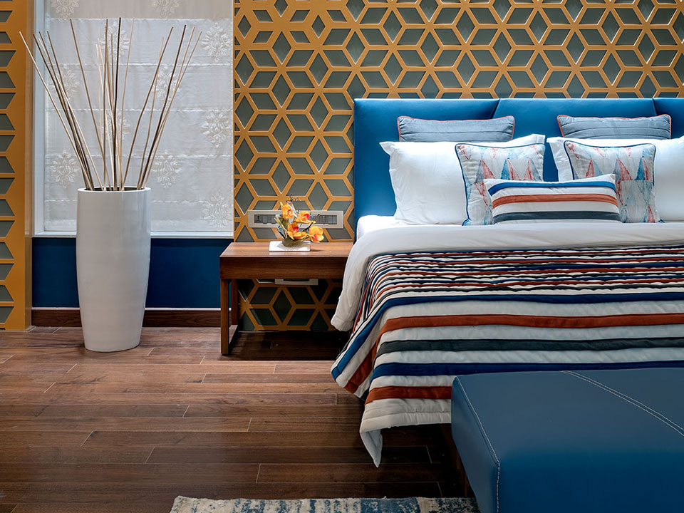 A bedroom with geometric patterns on the wall and wooden flooring along with blue bedding and furniture.