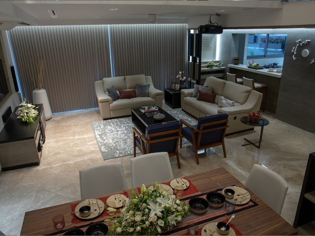 A dining and living area with neutral tones, a beautiful table and red accent artifacts and fabrics.