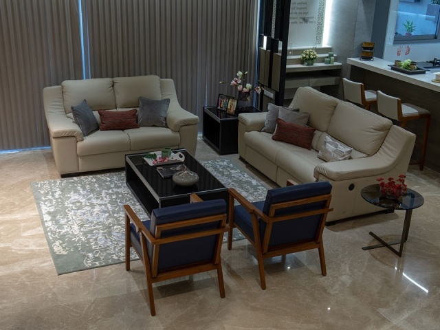 A stylish living room which is styled in a blue and white colour scheme with small artifacts.