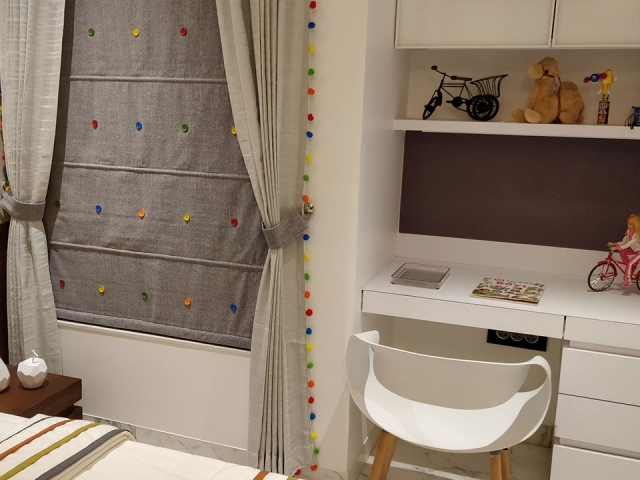 A study nook in a room styled with a white colour scheme and playful colourful curtains.