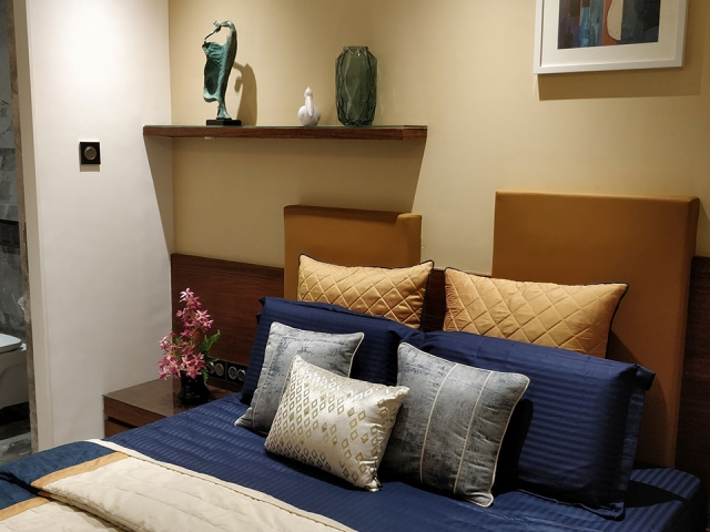 A bedroom with a large bed with an assortment of blue throw pillows and a general brown and beige colour scheme.