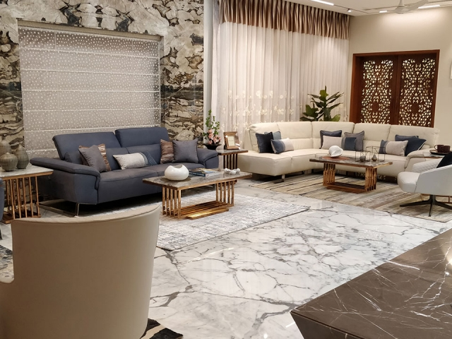 A spacious and personalized living room with white furnishings and rose gold toned accent pieces.