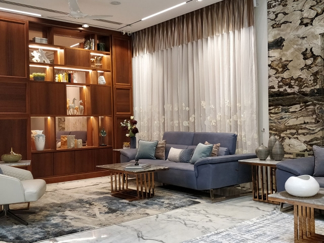 A spacious and personalized living room with a large wooden bookcase and blue and rose-gold furniture.