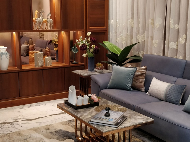 A spacious and personalized living room with blue furnishings and wooden wall decor.