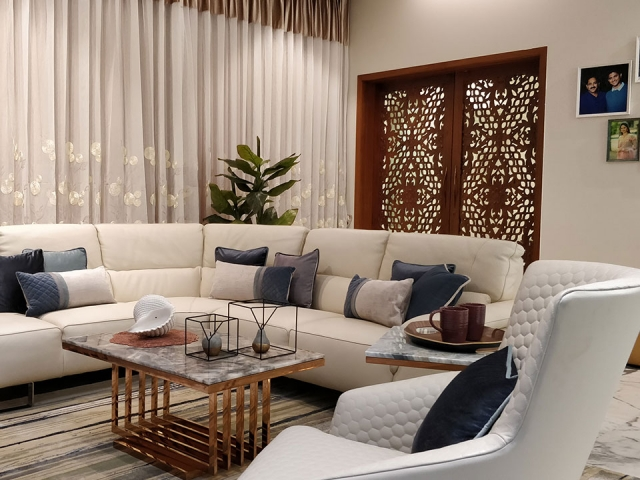 A spacious and personalized living room with white furnishings and unique centrepieces.