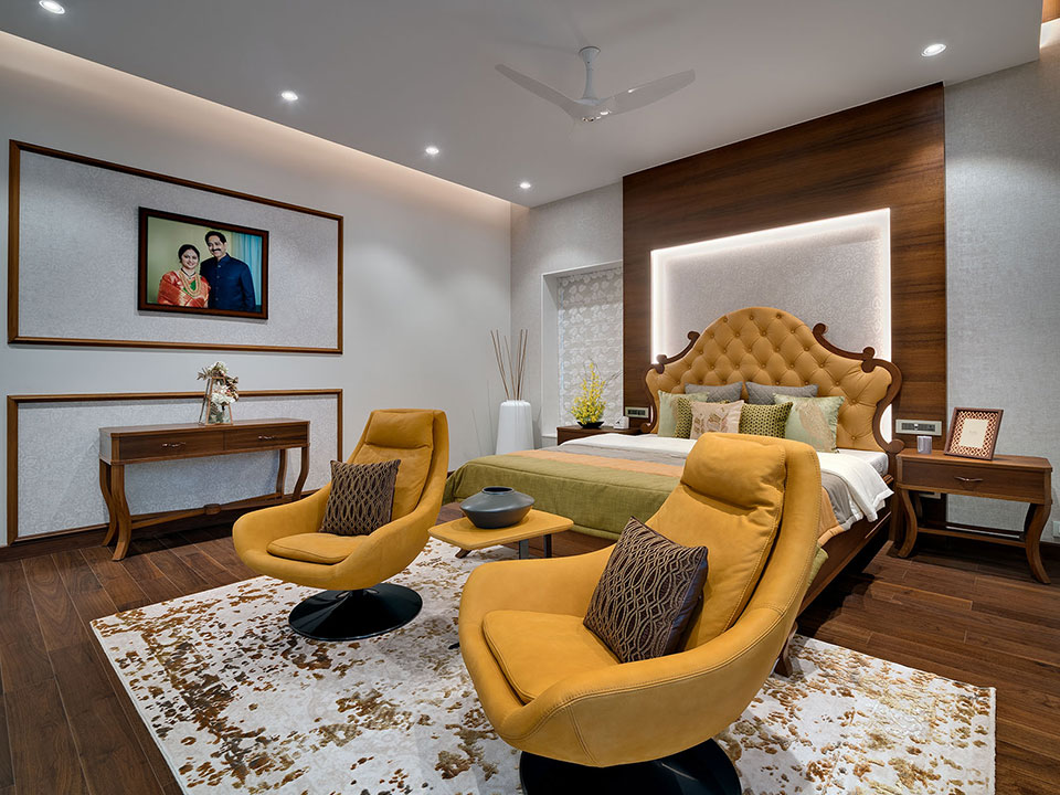 A large bedroom with wooden flooring and accents with orange furniture and personal mementos around the room.