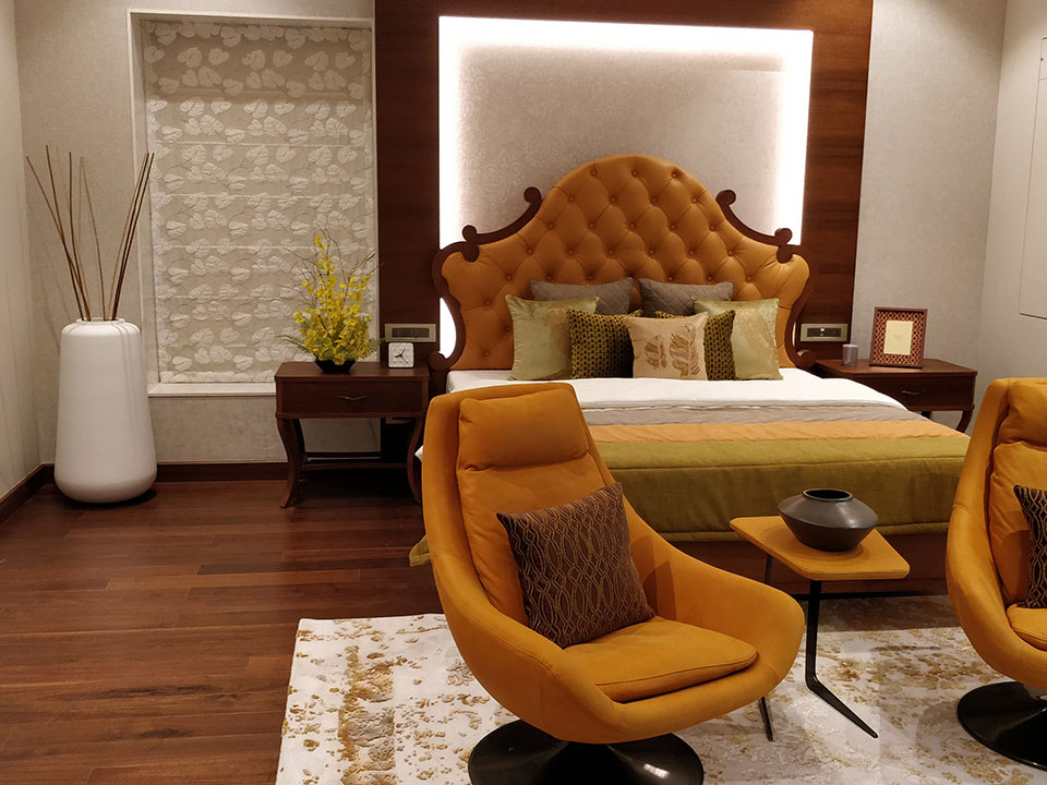 A bedroom whose interior has been styled with wooden furnishings and orange furniture and accessories.