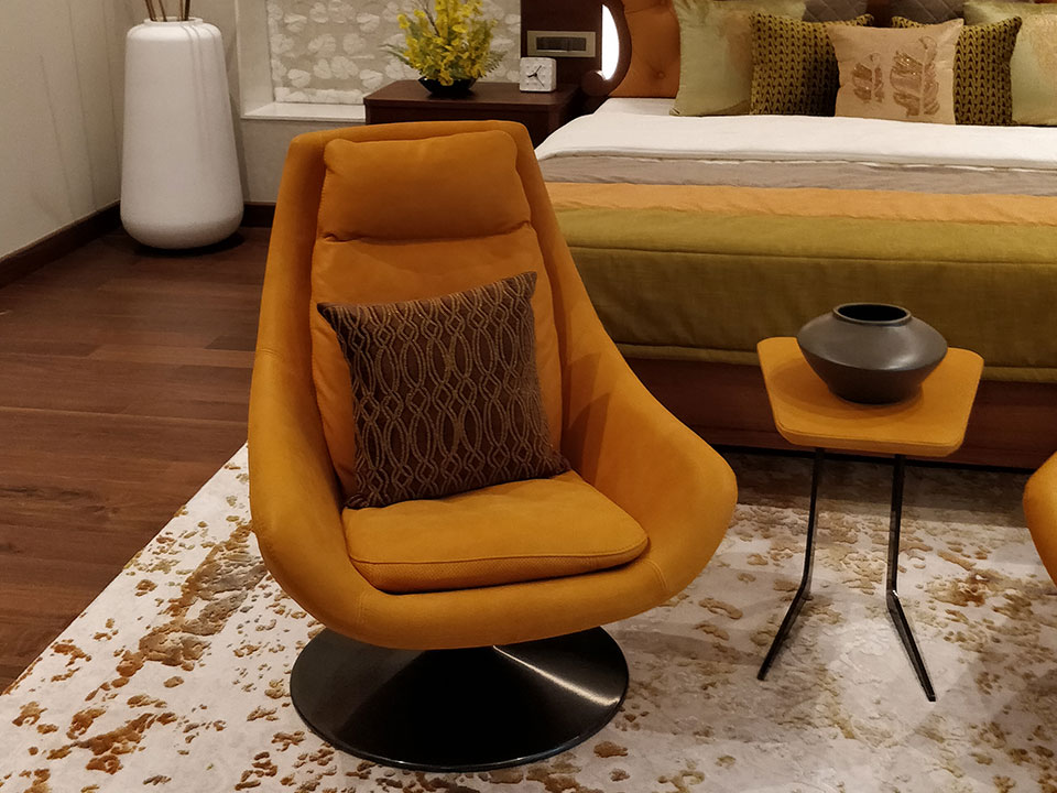 A close-up of a vibrant orange chair surrounded by other orange furniture and accessories in a room with dark wooden flooring.