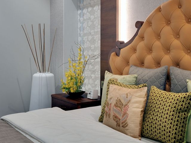 : A bed with a vibrant orange headboard behind colourful throw pillows and an elegant vase in the background.