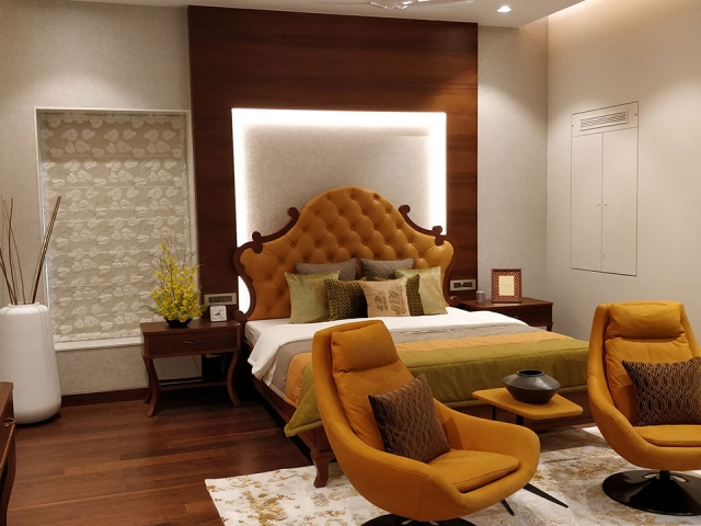 A well-lit bedroom whose interior has been styled with wooden furnishings and orange furniture and accessories.