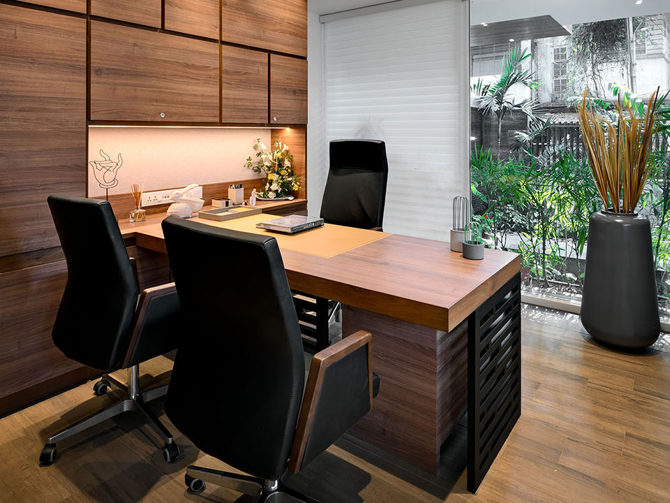 An elegant office space with wooden flooring and furnishings with a clear glass window overlooking a small patio filled with greenery.