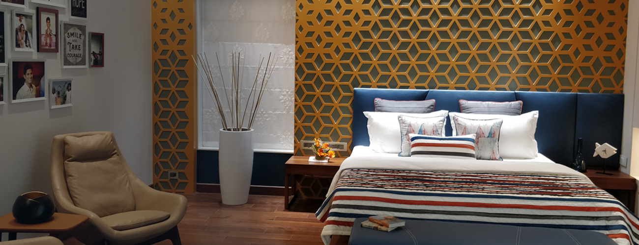 A beautiful bedroom whose interior has been styled and personalized with blue and white furnishings and brown accents.