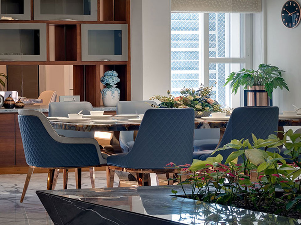 A beautiful dining area decorated in rich blues and surrounded by plants and nature.