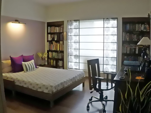 A bedroom with a large bed, a study space and many books on the bookshelves built into the walls.