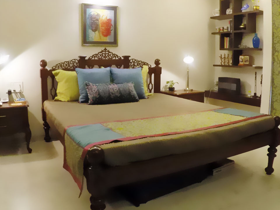 A large bed with a yellow and blue colour scheme for the bedding and wooden shelves on the wall.