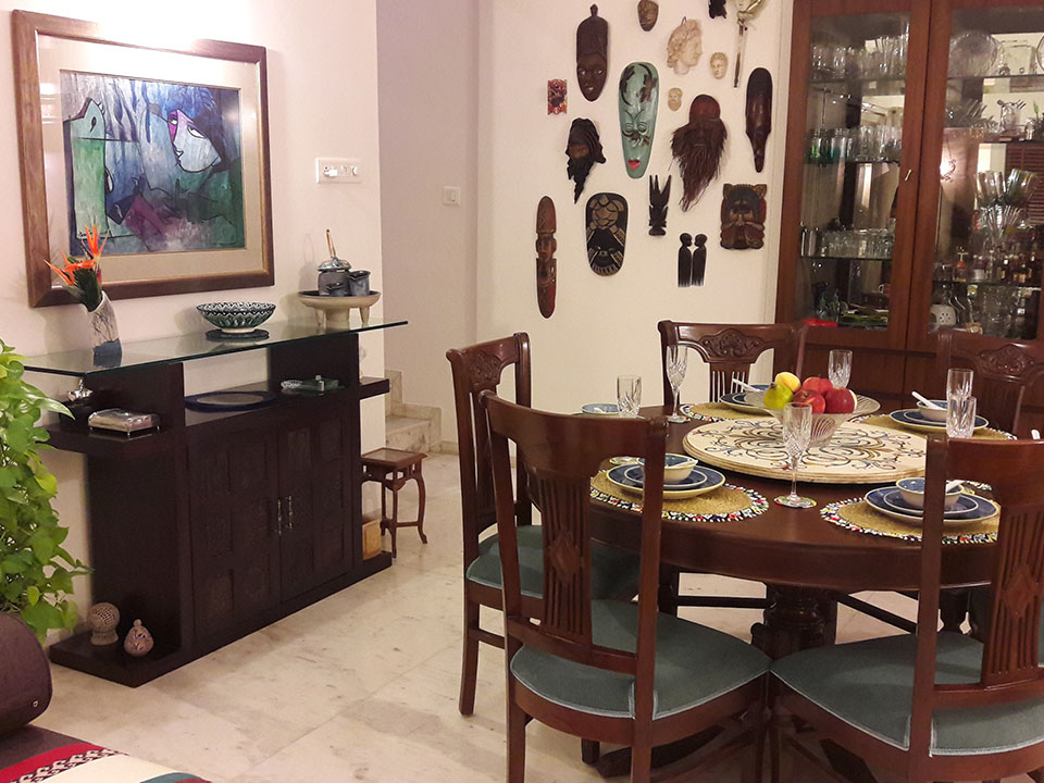 A dining room with interesting decorations on the wall, a wooden dining table and many patterns through the room.