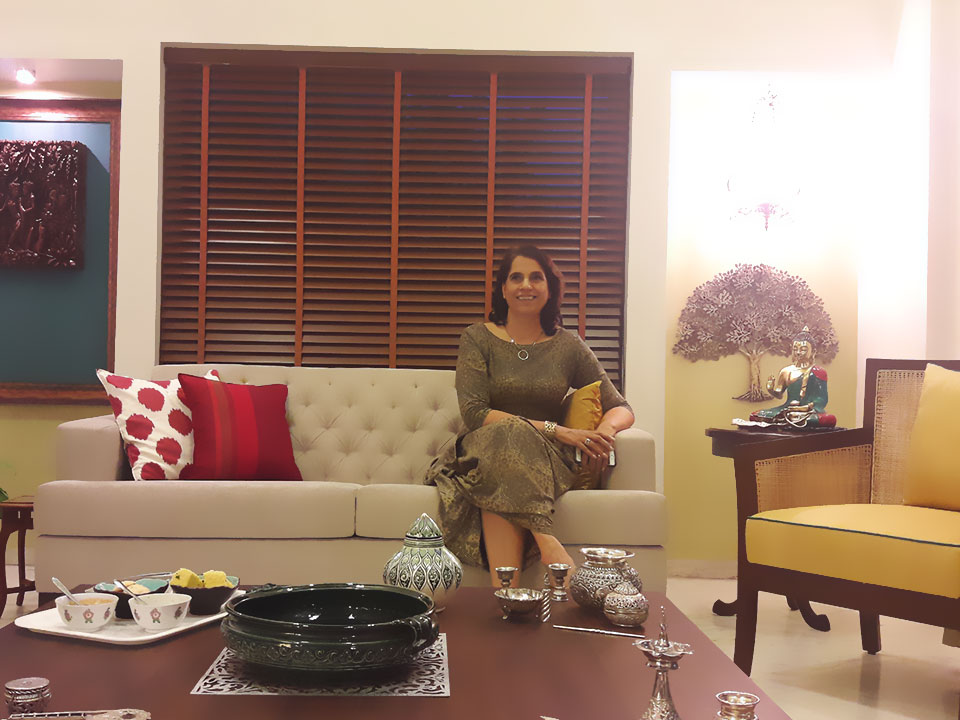 A smiling woman sitting on the white sofa in the living room which is decorated with many Indian metal artifacts on the walls and tables.