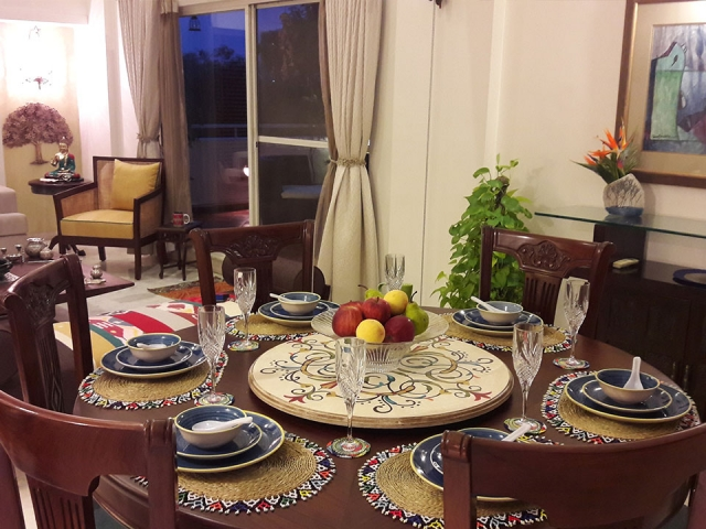 A circular dining table with colourful tablemats, an intricate turntable in the centre and a bowl of fruits.