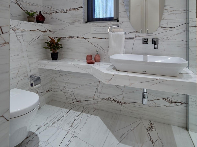 A elegant bathroom with marble flooring and walls in a white colour scheme with a peach pop of colour.