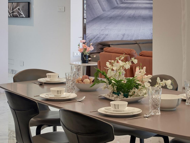 A grey dining table with an elaborate white flower arrangement and white crockery.