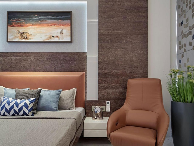 A sitting area in the bedroom in a neutral colour scheme with an orange brown chair and headboard.