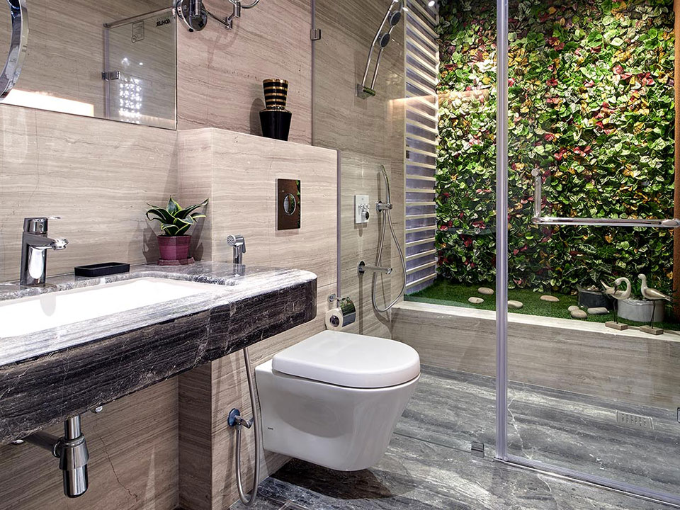 A beautiful bathroom in neutral colours with glass panels and a faux garden arrangement inside the shower cubicle.