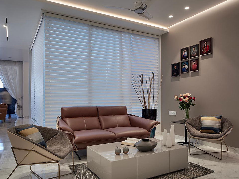 A sitting area in the living room with modern sofas in neutral tones, a minimalistic centre table and personal family photos on the wall.