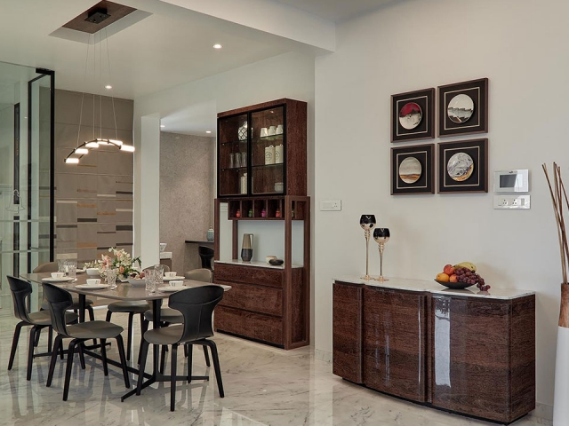A dining are with a grey dining table and wooden shelving and cabinets along the wall with beautiful styled artifacts.