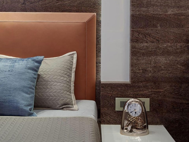 A bedside table styled with a small metal clock and a bed with neutral bedding and blue and orange accent pieces.